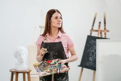 A young woman painter in a bright white studio draws a picture on canvas on an easel. Pink checked shirt, black apron, on the background of the pattern and stock photos