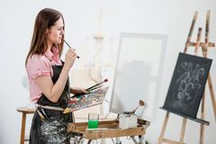 A young woman painter in a bright white studio draws a picture on canvas on an easel. Pink checked shirt, black apron, on the background of the pattern and royalty free stock photos