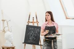 A young woman painter in a bright white studio draws a picture on canvas on an easel. Pink checked shirt, black apron, on the background of the pattern and stock images