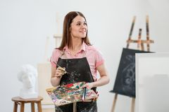 A young woman painter in a bright white studio draws a picture on canvas on an easel. Pink checked shirt, black apron, on the background of the pattern and royalty free stock photo