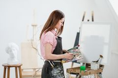 A young woman painter in a bright white studio draws a picture on canvas on an easel. Pink checked shirt, black apron, on the background of the pattern and royalty free stock images
