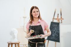 A young woman painter in a bright white studio draws a picture on canvas on an easel. Pink checked shirt, black apron, on the background of the pattern and stock photo