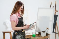 A young woman painter in a bright white studio draws a picture on canvas on an easel. Pink checked shirt, black apron, on the background of the pattern and stock image