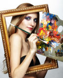 Young woman painter in golden frame with color pallet and paint Royalty Free Stock Image