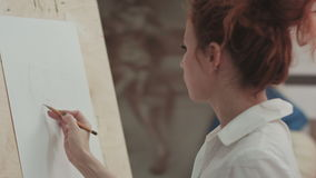 Young woman painter making sketches on blank canvas in artist workshop stock video