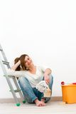 Young woman painter sitting on floor. Royalty Free Stock Image
