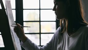Young woman is painting. Backlight close up. Relaxed creative atmosphere. Video footage. Artist young woman is painting. Backlight close up. Relaxed creative stock video footage