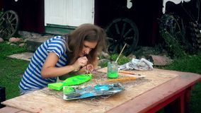Young woman painting fish decoration on wooden table in house yard stock footage
