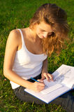 Young woman painting on a green meadow Stock Photos
