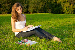 Young woman painting on a green meadow Royalty Free Stock Photo