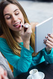 Young woman painting her lips with a digital tablet in a coffee Stock Image