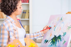 Young woman is painting a nature mort Royalty Free Stock Image