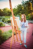 Young woman painting in park Stock Photos