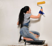 Young woman painting with a roller Stock Photography