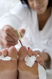 Young woman painting toe nails, close-up Stock Photography