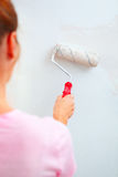 Young woman painting wall Stock Image