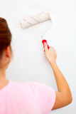 Young woman painting wall. With roller brush Royalty Free Stock Images
