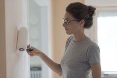Woman painting walls at home with a paint roller. Young woman painting walls at home with a paint roller: home makeover concept stock photography