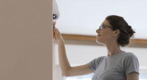 Woman painting walls at home with a paint roller. Young woman painting walls at home with a paint roller: home makeover concept stock images