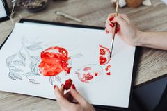 Young woman painting with watercolor paints stock images