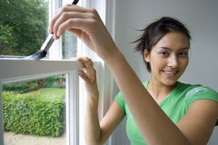 Young woman painting window frame, smiling, portrait, close-up Stock Image