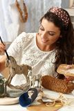 Young woman painting wooden horse Royalty Free Stock Photos