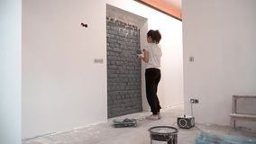 Young woman paints brick wall in gray colour using brush