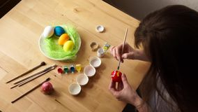 A young Woman Paints Easter Egg with a Brush on the background of Wooden Table stock video footage