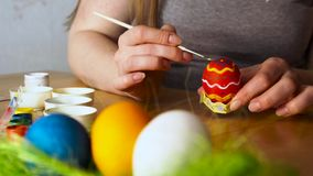 A young Woman Paints Easter Egg with a Brush on the background of Wooden Table