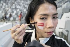 Young woman paints flag of Indonesia on her face. Close up of a young woman paints flag of Indonesia on her face before a sport match royalty free stock images