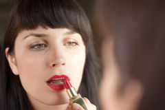 Young woman paints her lips red Stock Photo