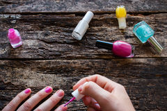 Young woman paints her nails pink polish on table Stock Photo
