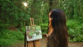 Young woman paints a landscape with oil painting in park. She straightening her hair, looks at nature and then at her picture. Makes a few touches. Slow motion stock video
