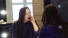 Young woman paints lips in photo studio. Media. Woman fixing make-up tinting lips in mirror with light bulbs. Dressing. Room in photo studio stock footage