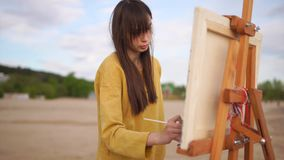 A young woman paints a paintbrush with a still-life on an easel, on the open air. A young woman painter paints a paintbrush with oil paints a still-life on an stock video footage