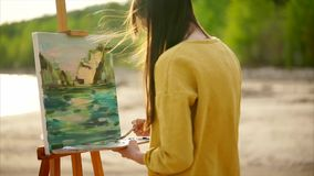 A young woman paints a painting on canvas, which stands on an easel. A young woman with long hair that develops in the wind paints a picture on canvas, which stock video footage