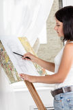 Young woman paints a picture Stock Photography