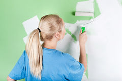 Young woman paints the wall Stock Images