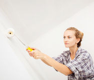 Young woman paints the wallpaper roll Stock Photos
