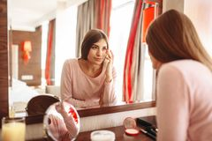 Young woman in pajama in front of the mirror. In the bedroom. Female person cares for skin. Morning facial cleaning procedure royalty free stock images