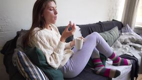 Young woman in pajama pants sits on a sofa and eats marshmallows from a white coffee mug. 4k stock footage