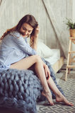 Young woman in pajama wake up in the morning in cozy scandinavian bedroom and lying on bed with oversize knitted blanket. Casual lifestyle in modern interior Royalty Free Stock Photos