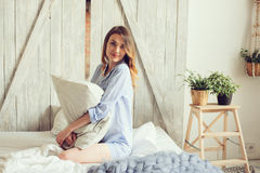 Young woman in pajama wake up in the morning in cozy scandinavian bedroom and lying on bed with oversize knitted blanket Stock Image