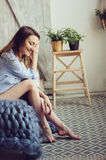 Young woman in pajama wake up in the morning in cozy scandinavian bedroom and lying on bed with oversize knitted blanket Stock Photography