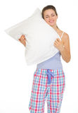 Young woman in pajamas enjoying cosy pillow Stock Photography