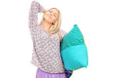 Young woman in pajamas holding pillow and stretching herself Royalty Free Stock Photos