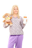 Young woman in pajamas holding teddy bear and baby bottle Royalty Free Stock Photos