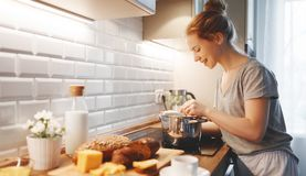 Young woman in pajamas prepares breakfast in morning Royalty Free Stock Photo