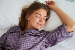 Young woman in pajamas sleeping peacefully on her back with one. Young brown-haired woman in pajamas is sleeping peacefully on her back with one hand resting on Royalty Free Stock Photos