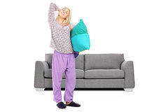 Young woman in pajamas stretching in front of a sofa Royalty Free Stock Image